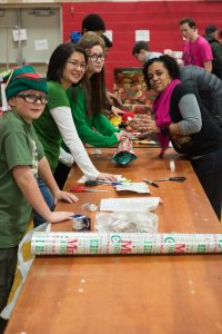 Volunteers wrap presents for the children attending the Christmas party.
